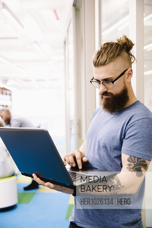 Creative businessman with tattoos using laptop in office