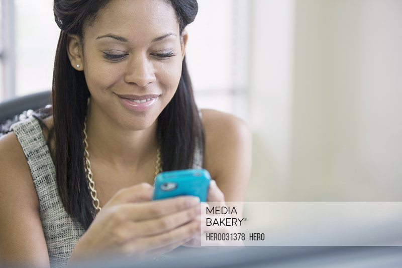 pretty african american woman texting on smartphone