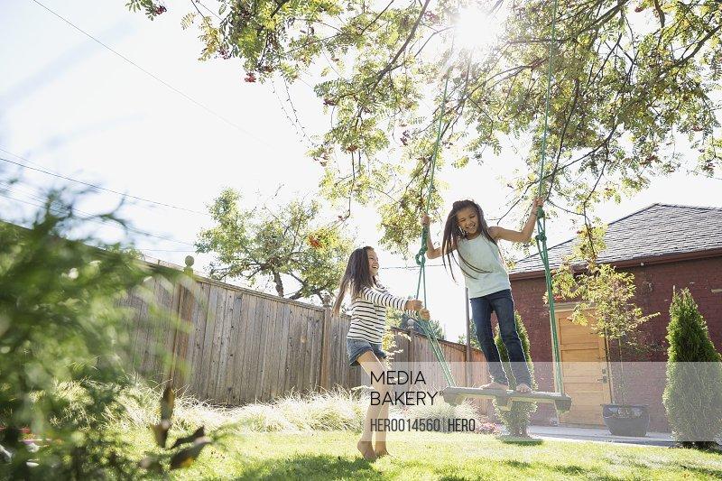 Sisters playing on tree swing in backyard