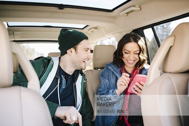 Happy couple using smart phone in back seat of SUV