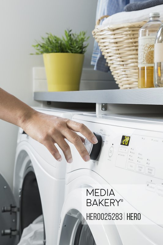 Woman turning washing machine dial in laundry room