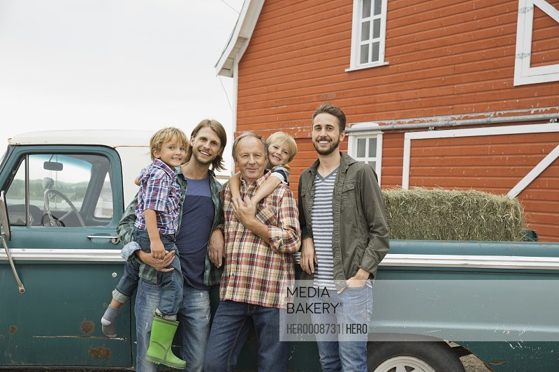 Happy three generation male family standing by pick-up truck