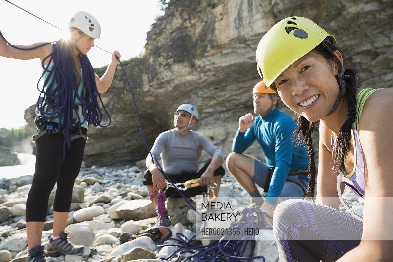 Portrait smiling woman preparing rock climbing equipment