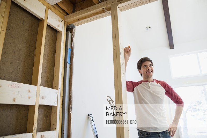 Smiling man leaning on beam in home