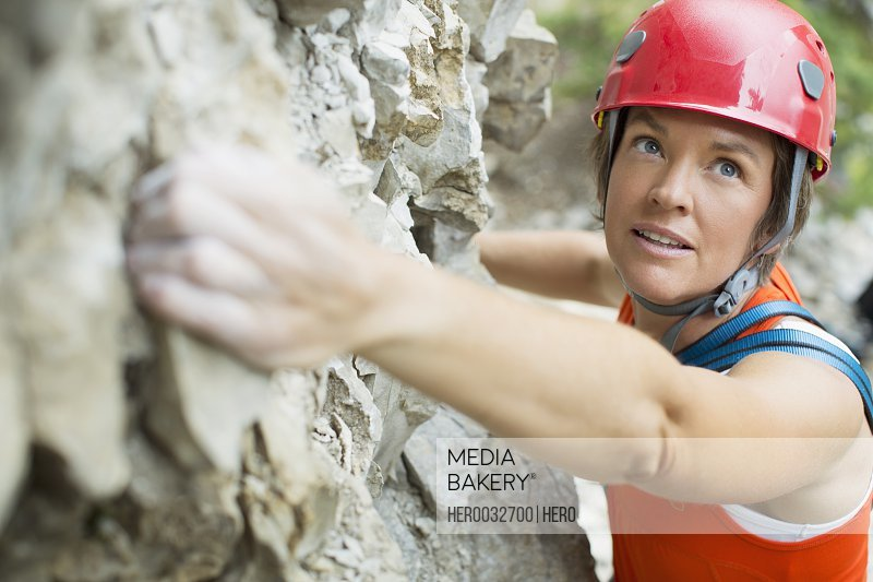 middle-aged female rock climber on rock face