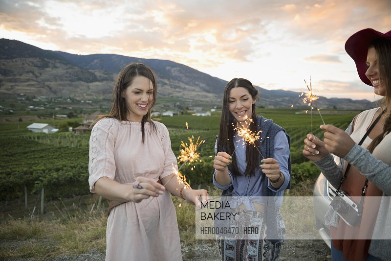 Women friends with sparkler fireworks in vineyard