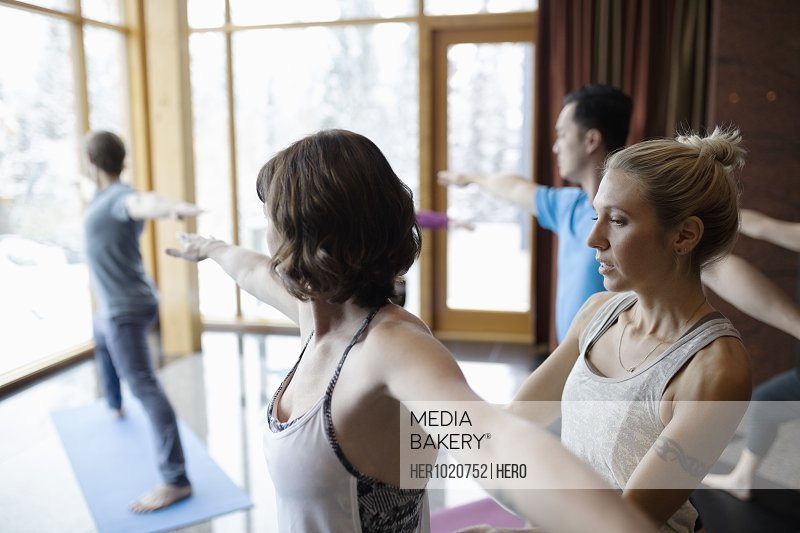 Instructor helping woman practicing warrior 2 pose in yoga class studio
