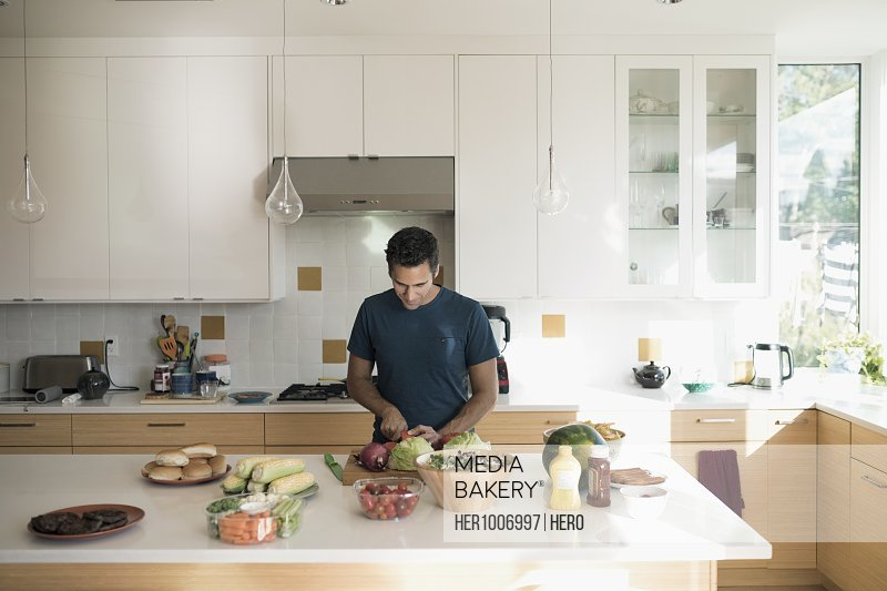 Man cooking, cutting vegetables on cutting board on kitchen counter