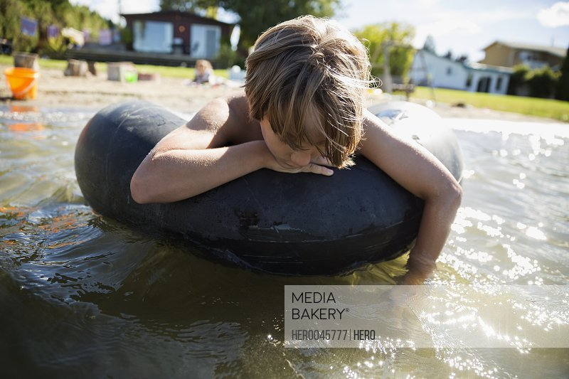 Boy floating on inner tube on sunny summer lake
