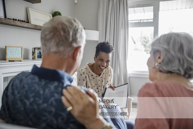 Financial advisor discussing paperwork with senior couple in living room