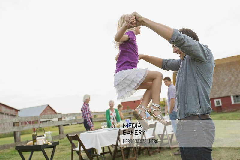 Father lifting young daughter into the air.