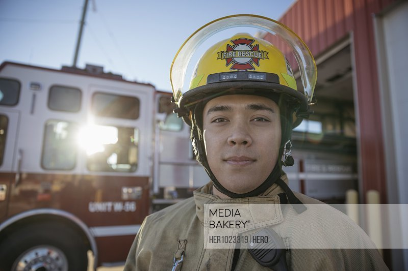 Portrait confident, tough male firefighter standing outside fire station