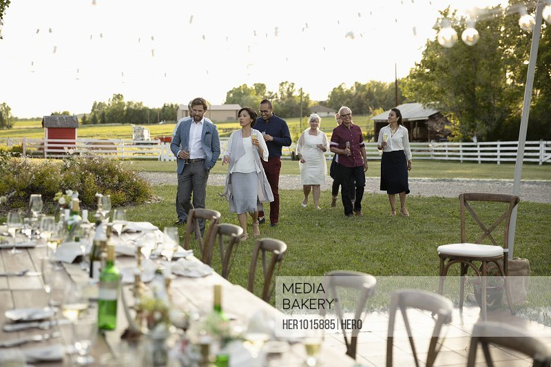 Friends walking toward wedding reception tables in rural garden