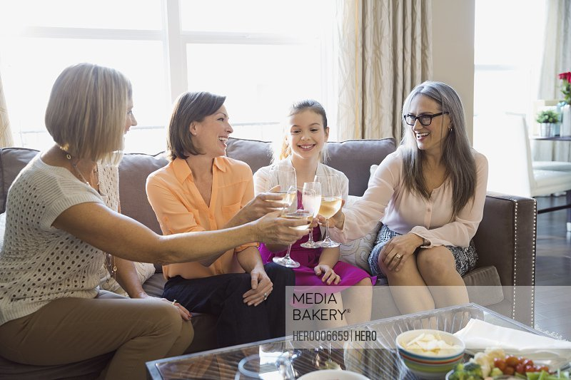 Women toasting wineglasses at home