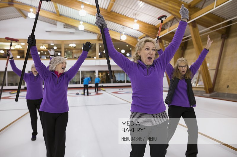 Enthusiastic women curling and cheering