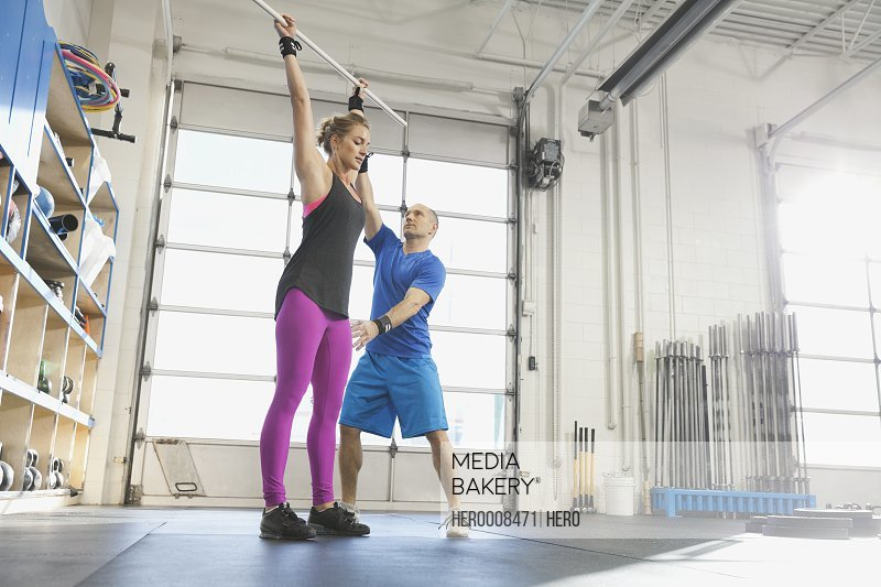 Gym instructor practicing lifting technique with woman