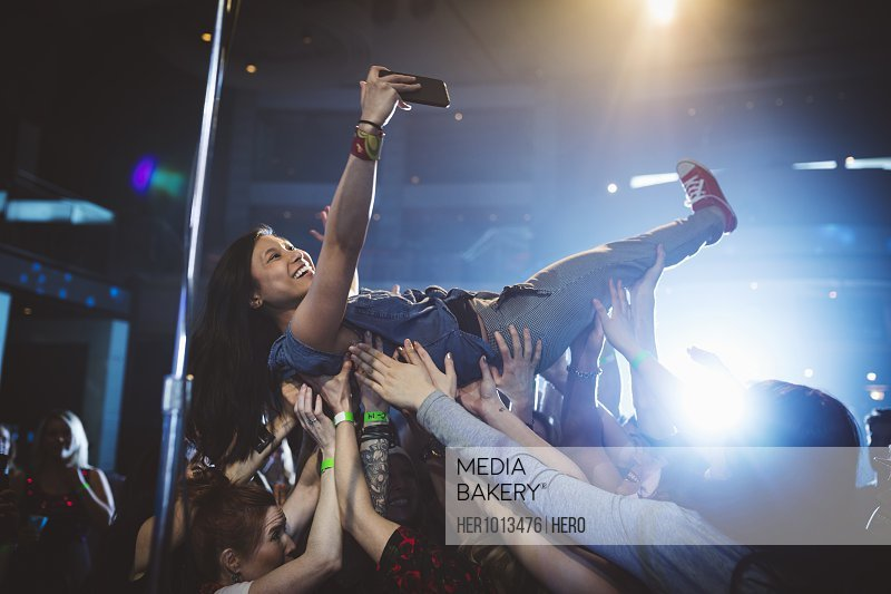 Exuberant woman with camera phone crowdsurfing at music concert in nightclub