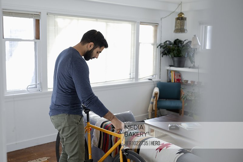 Man with bicycle in living room