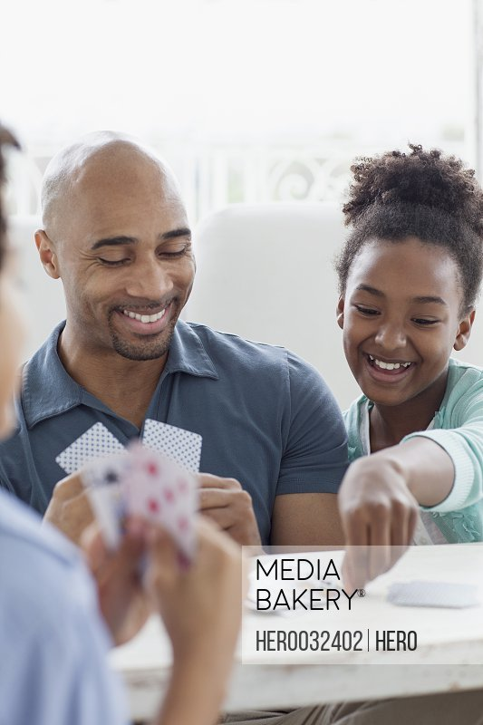 father playing cards with son and daughter