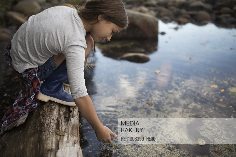 Curious girl on fallen log reaching for tidal pool water