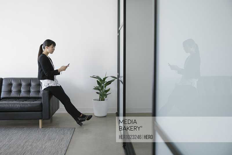 Businesswoman using smart phone in office lobby