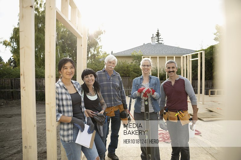 Portrait smiling, confident volunteers helping build house
