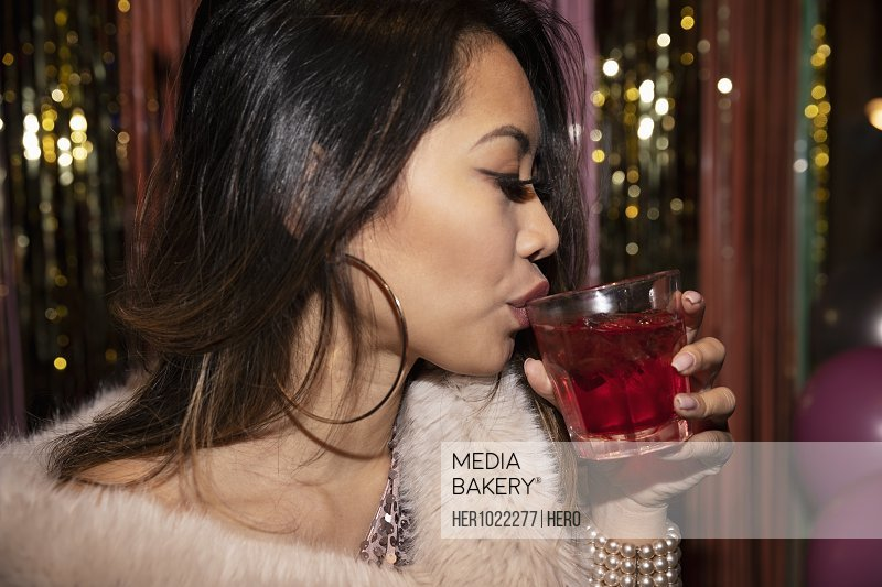 Woman drinking cocktail at party