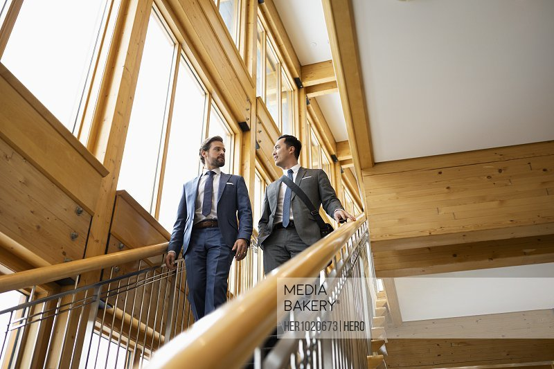 Businessmen talking and descending hotel stairs