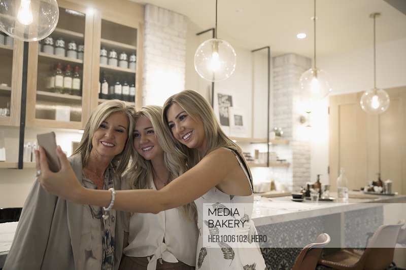 Blonde mother and adult daughters taking selfie in salon