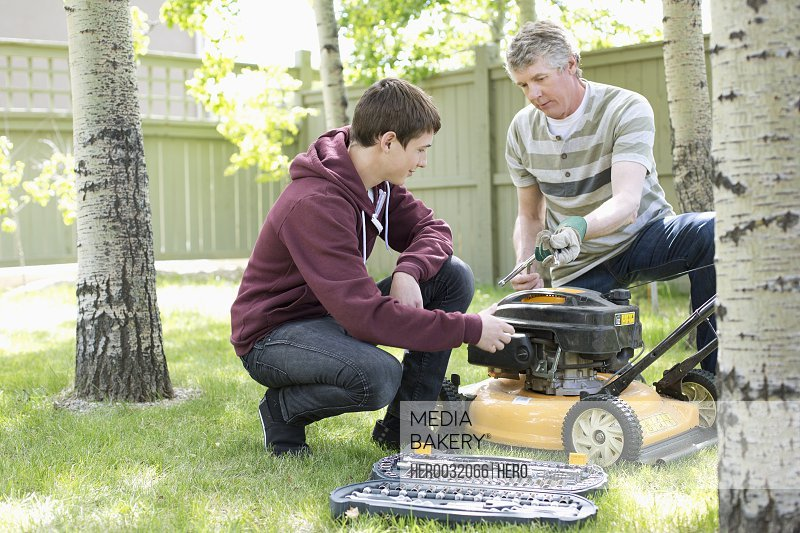 father and son maintaining lawn mower