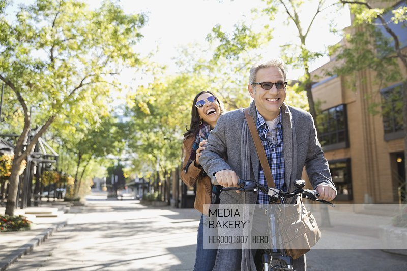 Smiling couple riding bicycle