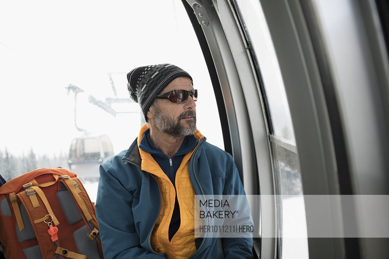 Senior male skier riding gondola