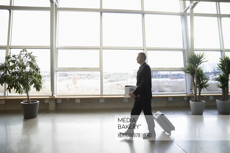 Businessman walking with suitcase in office lobby