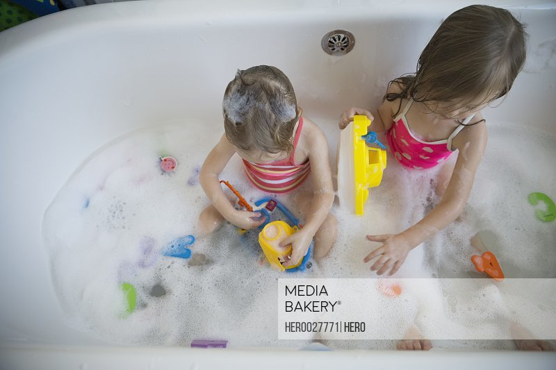 Overhead view sisters playing with toys bubble bath