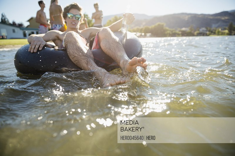 Young man floating in inner tube at sunny summer lake