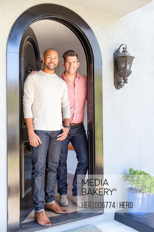 Portrait smiling male gay couple standing in house doorway