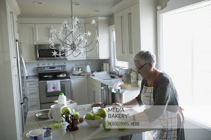 Senior woman rolling pie crust dough with rolling pin in kitchen