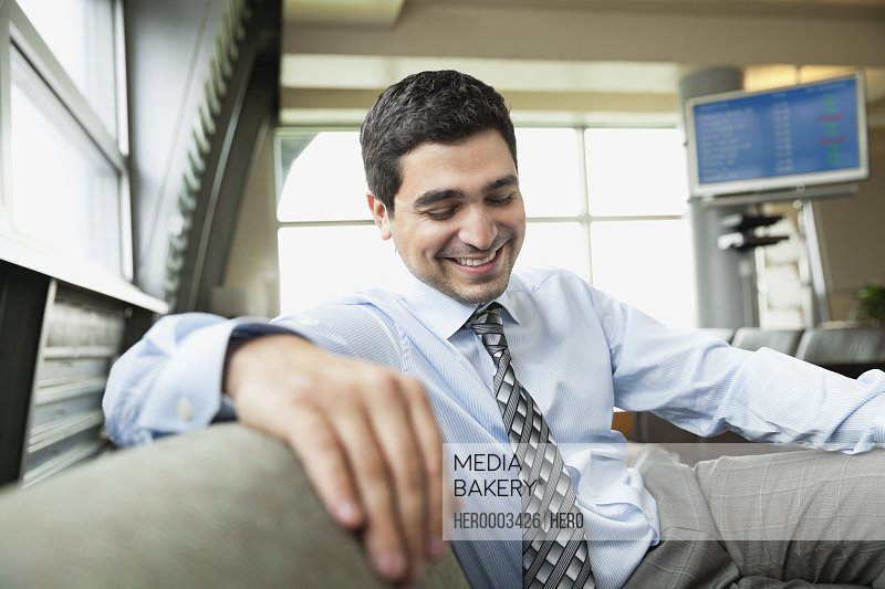 Smiling businessman looking down