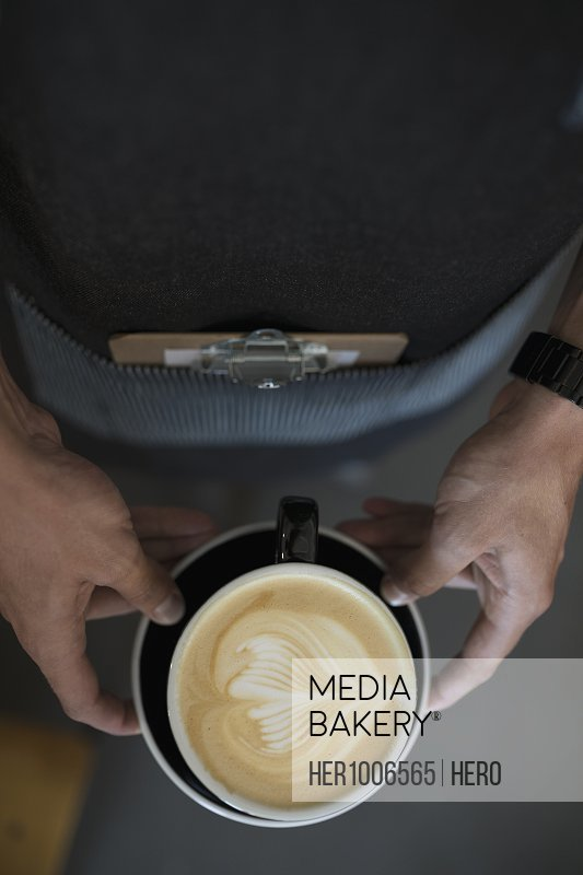 Overhead view male barista holding cappuccino with creative milk foam leaf pattern in coffee cup