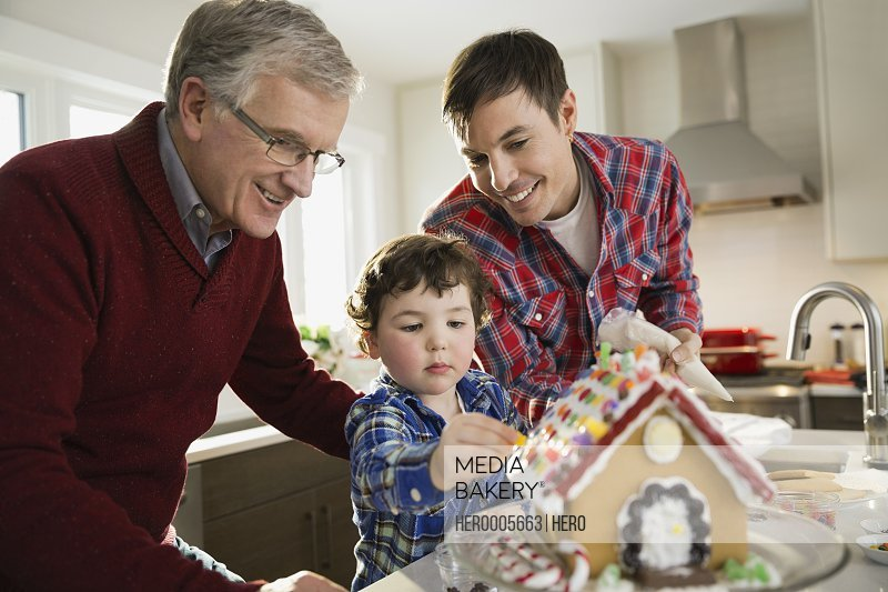 Three generation family decorating gingerbread house together