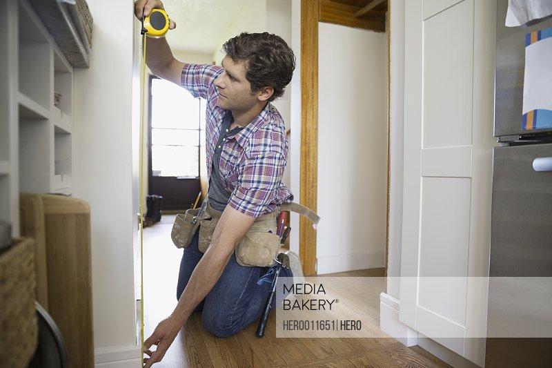 Man measuring wall with tape measure