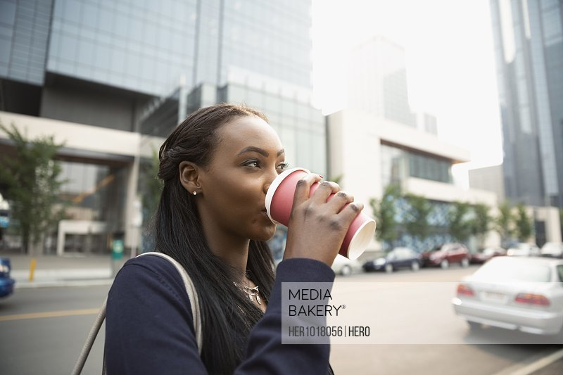Businesswoman drinking coffee on city street