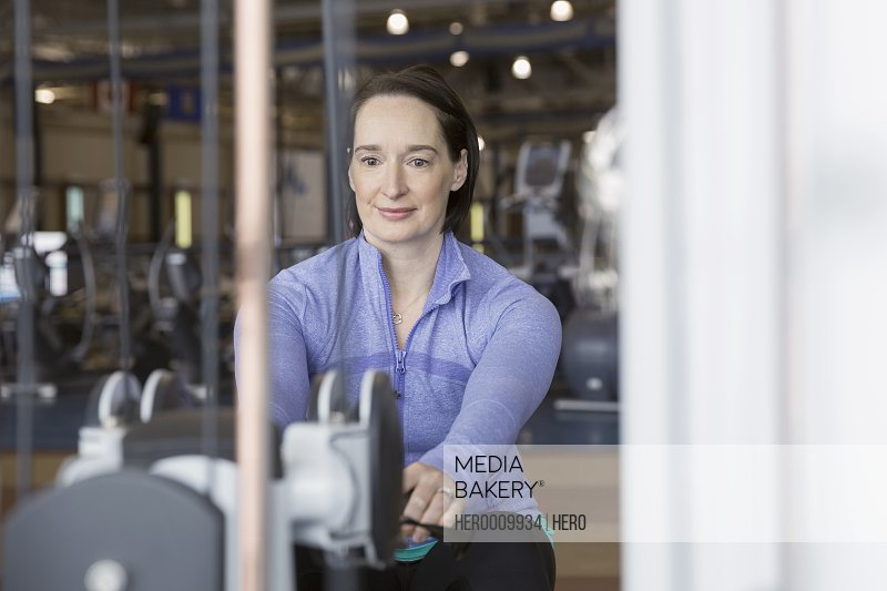 Woman using weight machine at gym