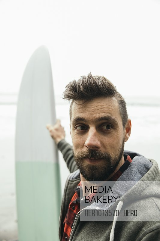 Confident male surfer holding surfboard