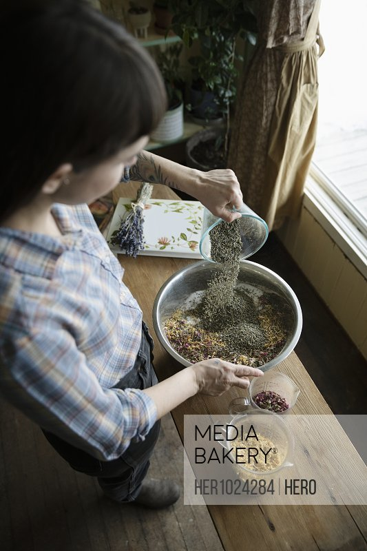 Female business owner mixing dried flowers in apothecary