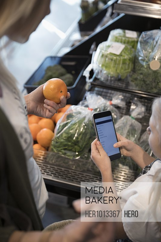 Mother and daughter with smart phone list grocery shopping in produce section at market