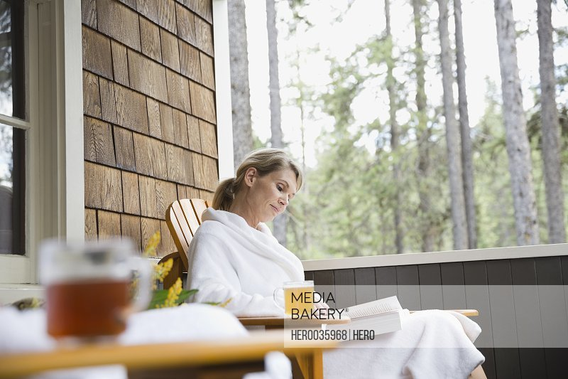 Woman relaxing on porch with a book