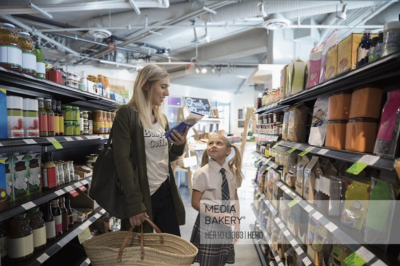 Mother and daughter in school uniform grocery shopping in market aisle