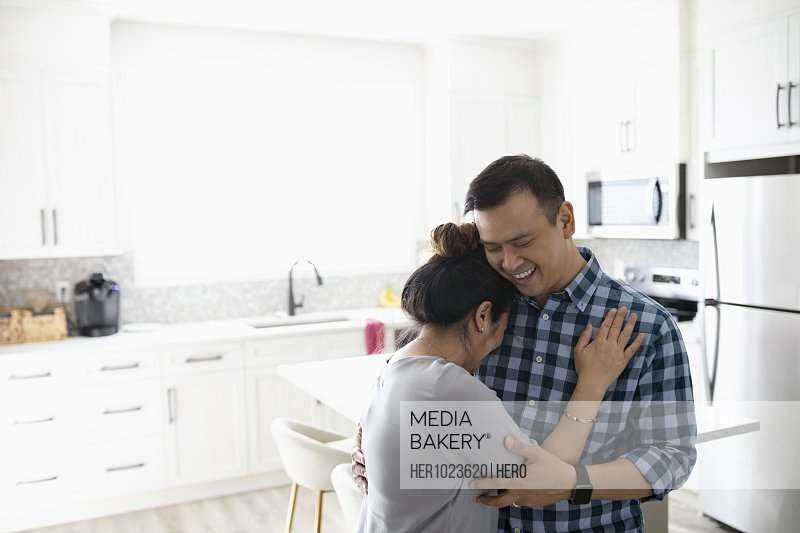 Happy, affectionate couple hugging in kitchen