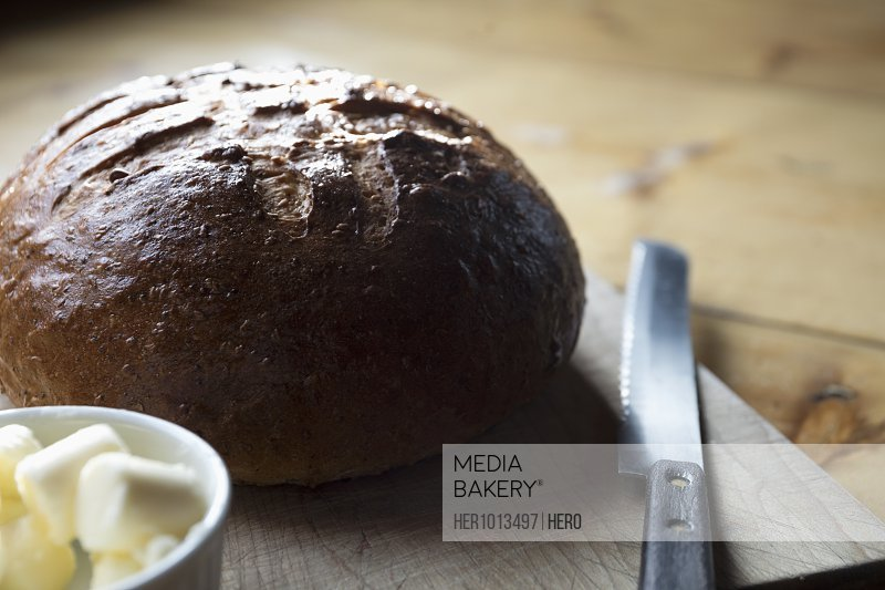 Rustic, homemade bread loaf on cutting board with butter and knife